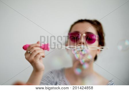 Close up side view shot of young female model blowing soap bubbles on white background. Focus on hands and wand.