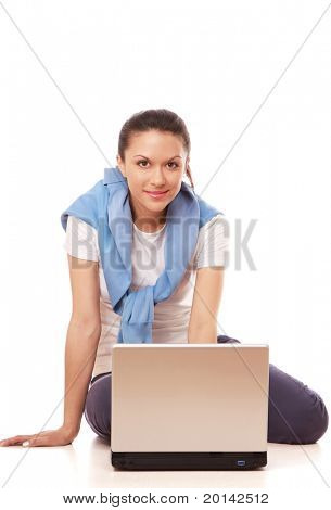 A young woman sitting on the floor with a laptop