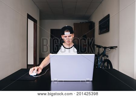 Conceived young man looking at a laptop while working at home