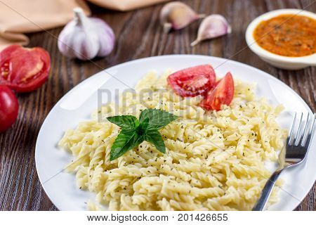Macaroni pasta spiced with oregano and basil herbs, ready to eat with tomato and garlic sauce, top view