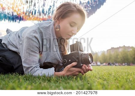 Pretty caucasian female using film photocamera and smiling. Traveling woman taking photo on vintage camera outdoor in summer