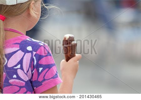 Young Girl Eating Icecream On A Hot Day In Summer