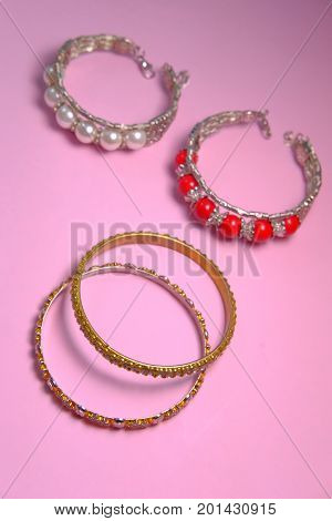 bangles and red pearls isolated with pink.