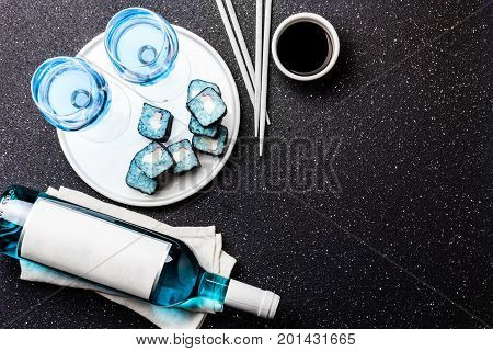 Blue sushi rolls and blue wine chardonnay on black background. Spanish blue wine, trendy drink, Fancy wine, top view. Copy space.
