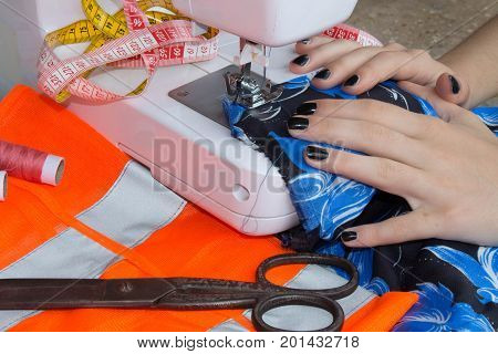 Woman hand on sewing machine.Dressmaker work on the sewing machine. Hobby sewing fabric as a small business concept. Dressmaker woman working with sewing machine