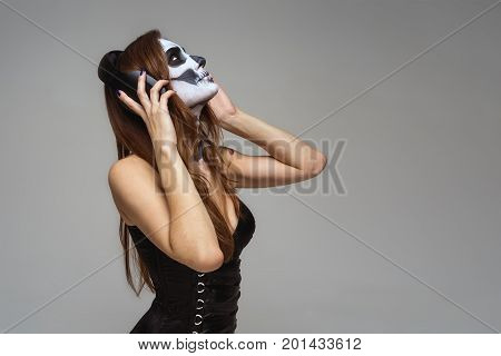 Portrait of young beautiful girl with fearful halloween skeleton makeup Katrina Calavera in headphones listening to music on gray background