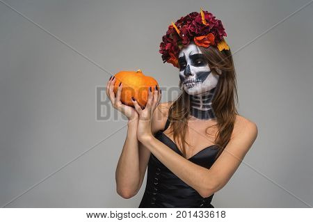 Portrait of young beautiful girl with fearful halloween skeleton makeup with a wreath Katrina Calavera made of flowers on her head holding pumpkin over gray background
