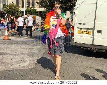 SOUTHAMPTON UK - August 26 2017: Southampton Pride 2017 City's second annual Pride event in Southampton UK. Woman wearing rainbow boa and carrying pink inflatable animal.