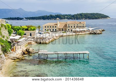Corfu Greece - June 7 2017: Faliraki beach (Alecos Baths) - one of the oldest public bathing spots with the En plo restaurant in Corfu Town.