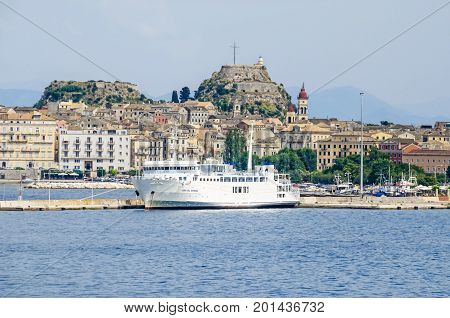Corfu Greece - June 7 2017: Old Corfu town with the Venetian Old Fortress the bell tower of the Saint Spyridon Church and a ferry boat as seen from the harbor