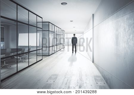 Back view of young businessman in modern office hallway interior with equipment city view and daylight. Research conept. 3D Rendering