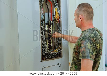 Professional electrician installing components in electrical shield The electrician checks the shield