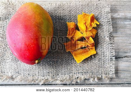 Raw organic dried mango and fresh ripe mango fruit on wooden rustic table.Dried mangos.Selective focus.