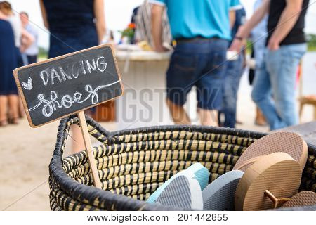 Decorative wicker basket with flip flops for use as dance shoes at a beach party