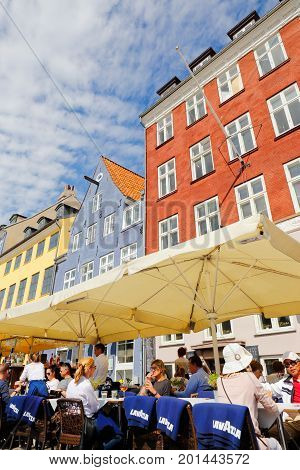 Copenhagen Denmark - August 24 2017: Restaurant guests at the outdoor seating in Nyhavn in front of the colorful old builds in the background.