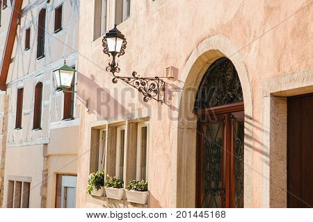Lantern on the wall of the house on a beautiful street with traditional houses in German style in Rothenburg ob der Tauber. Germany. Europe.