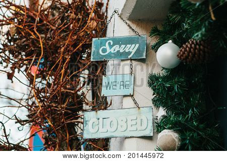 Signboard Sorry we are closed next to the Christmas decorations. The concept of the end of Christmas sales.