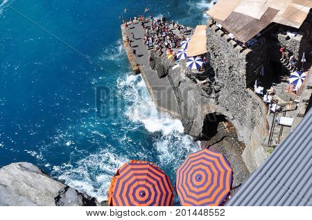 A stunning shot of Cinque Terre during the Summer months. An overhead shot of the beautiful blue Mediterranean Sea meeting the Italian rocky shore. Bright umbrellas complimenting and contrasting the brilliant blue water.
