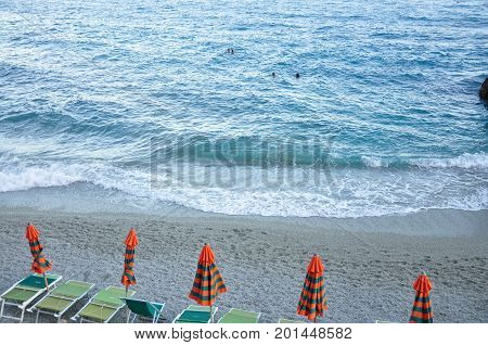 The sandy beaches of Cinque Terre in the Summer months. Large blue waves crashing on the sandy shore. Sun bathing chairs and umbrellas lined up.