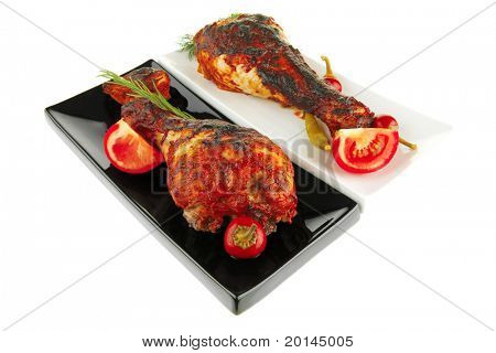 fresh roasted drumstick on ceramic plates with tomatoes