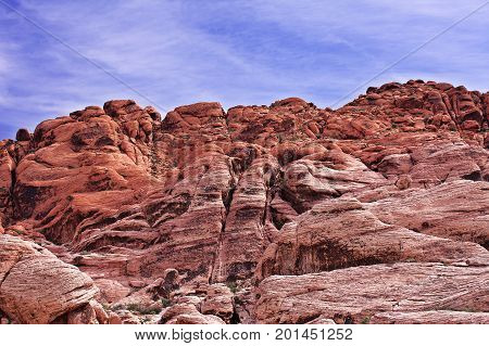 Looking upward at a cliff of jagged, craggy, red rocks with a blue, cloudy sky in the background. Red Rock, Nevada. There are small outcrops of dark green foliage and the rocks are cracked and eroded. The picture is highly textured.