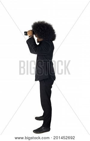 Side view of an Afro businessman standing in the studio while using a binocular isolated on white background