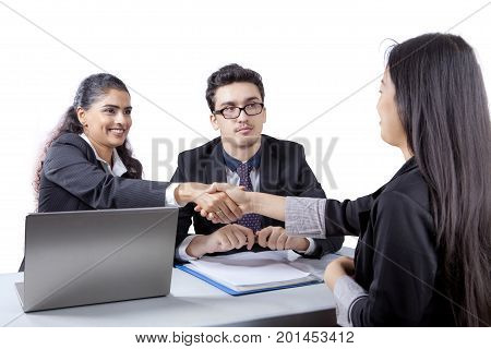Young business people giving a congrats sign by shaking hands on a new employee isolated on white background