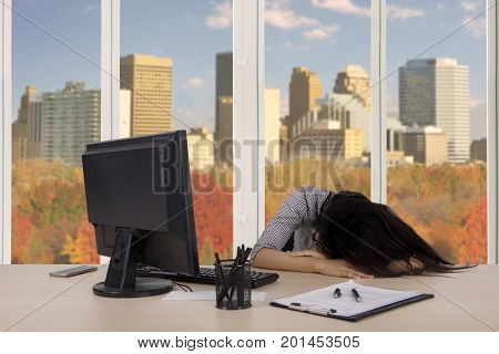 Portrait of young businesswoman looks sleep deprivation while working with a computer and paperwork