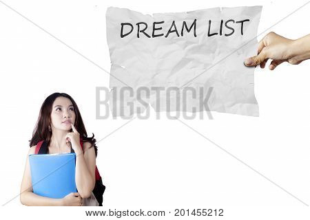 Female high school student holding a folder while looking at a text of dream list on the paper