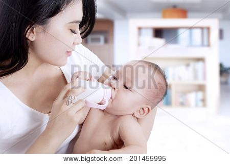 Portrait of cute newborn baby being fed by her mother using milk bottle in the home