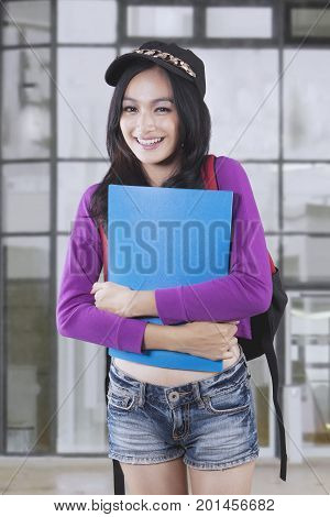 Potrait of pretty female student holding a folder while smiling at the camera and standing near a school building