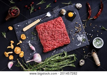 Chopped or minced meat with herbs berries and chanterelles. Restaurant cooking concept. Top view.