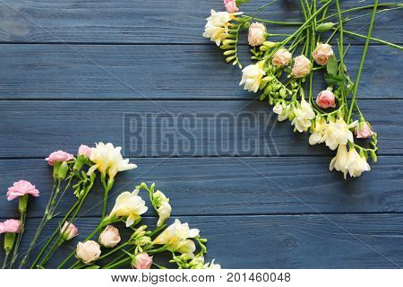 Beautiful composition with fresh freesia on dark wooden background