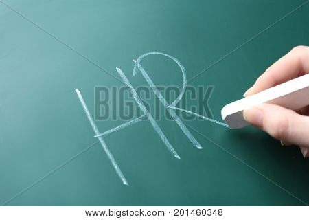 Female hand writing management abbreviation HR on chalk board