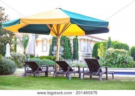 Comfortable sun loungers near swimming pool at resort