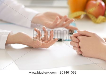 Hands of nutritionist and patient sitting at table in clinic. Weight loss concept