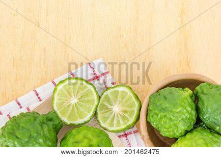 Close up fresh bergamot and bergamot slice in wooden bowl on dark wood table background. bergamot on old wooden brown with copy space. (Bergamot or Kaffir lime)