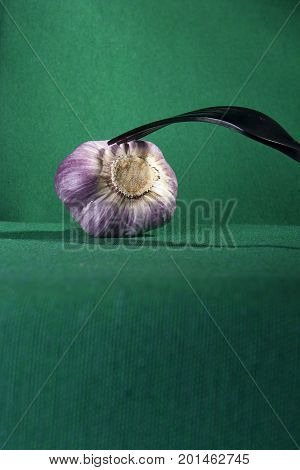 Fork and garlic on a green background