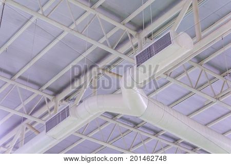 HVAC duct air conditioner ventilation pipes system in white insulation material hanging from the ceiling inside new building.