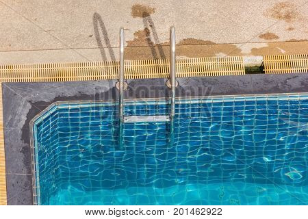 Swimming pool with metal handrail stair or Pool ladder Top view
