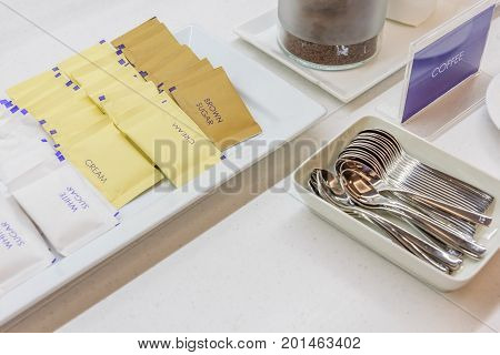 Coffee cream white and brown sugar sachet serve with silver spoon on white table.