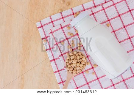 soy milk in glass bottle with soy beans in spoon on wooden background Top view with copy space and text.