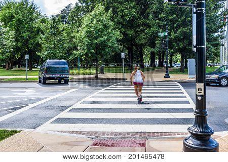 Washington Dc, Usa - July 1, 2017: Woman Jogging Crossing Street By Union Station On Columbus Circle
