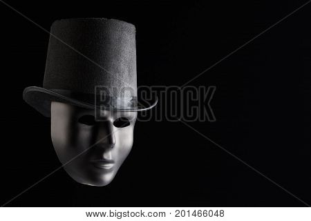 Black mask face wearing black top hat isolated on black background with copy space. Anonymity and mystery concept