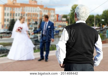 A Man Looks From Afar On The Newlyweds, A Parent.