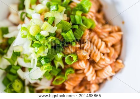Closeup Of Brown Rice Fusilli Pasta Bowl In Marinara Sauce Topped With Green Onions