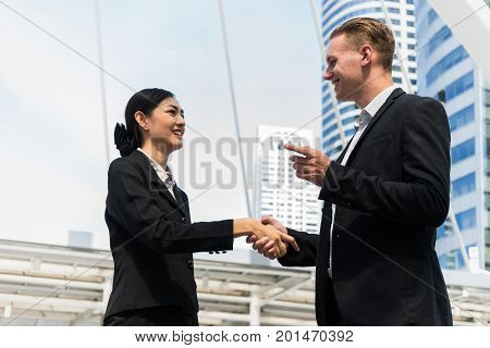 Businessman and Businesswoman shaking hands for demonstrating their agreement to sign agreement or contract between their firms / companies / enterprises. success dealing greeting and partner concept.