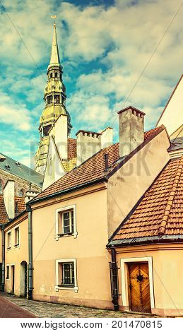 Medieval district in old Riga city that is the capital of Latvia offering for tourists unique architectural Gothic ensembles and rare ancient buildings. Image slightly toned for inspiration of retro style