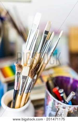 Macro closeup of many clean paintbrushes in cup on artist desk