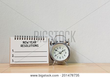 New year's resolution on a notebook and alarm clock on wood table Copy space